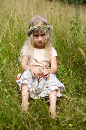 grass skirt: little long-haired blonde girl in wild flower wreath sitting at the meadow