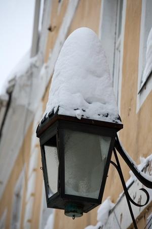 snowdrift: street lantern with big snowdrift hanging on house wall Stock Photo