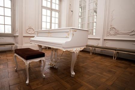 piano de cola: piano de cola blanco de pie en el interior de un elegante color blanco del palacio de salón Foto de archivo