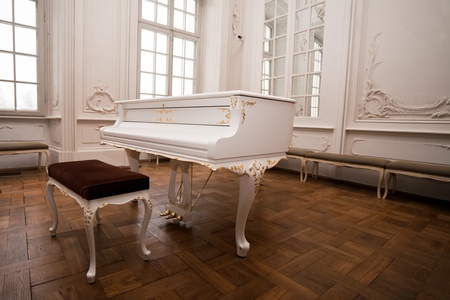 white grand piano standing in elegant white interior of  palace hall