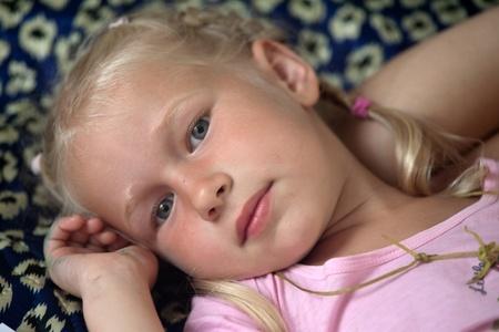 closeup portrait little blonde girl laying down Stock Photo