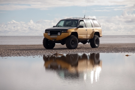 big four-wheel jeep standing beautifully between blue sky and sea water with reflection