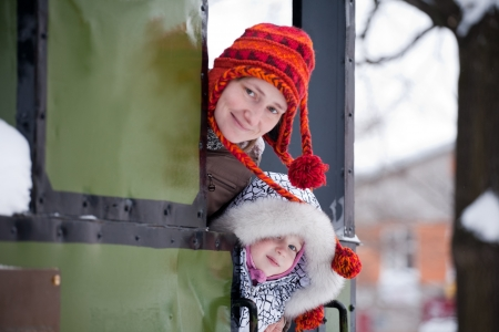 out door: mother and little daughter in winter hats looking out train door Stock Photo
