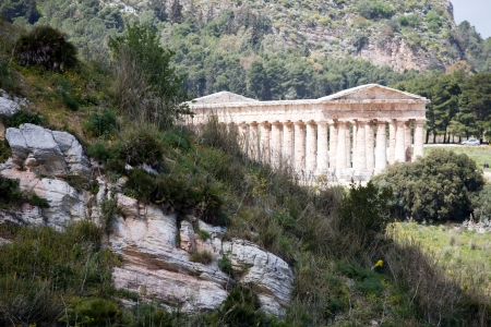 mountain landscape with a rock and white ancient Greek temple of Venus, Segesta village, Sicily, Italy photo