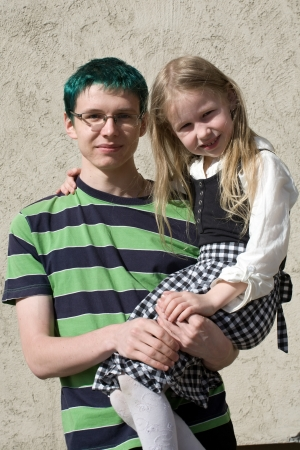 little fair-haired sister on her big green-haired brothers hands photo