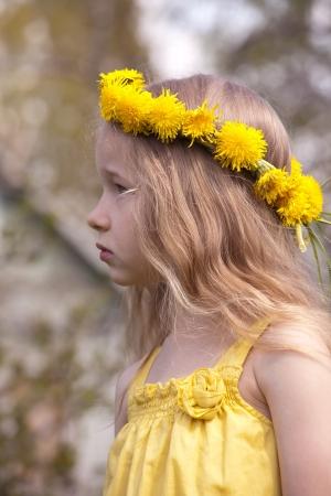 profile portrait of little fair-haired girl in dandelion wreath photo