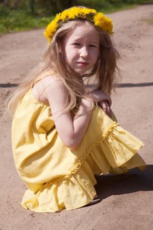 sundress: little fair-haired girl in dandelion wreath sitting in the squatting position
