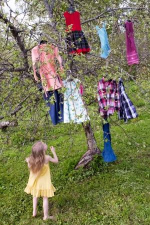 pensiveness: ragazza in piedi poco prima che l'albero con abiti appesi sui rami