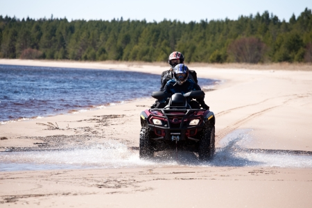 quad: two men riding small all-terrain vehicle on sandy coast of forest lake, front view