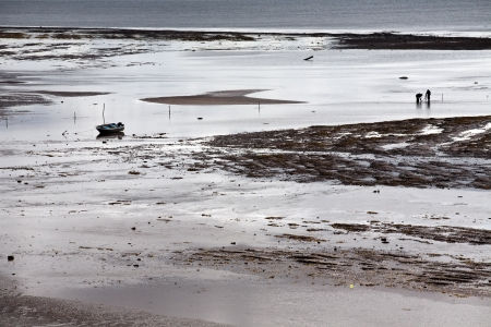 ebb: dwóch rybaków i ich łodzi na tle morza ebb