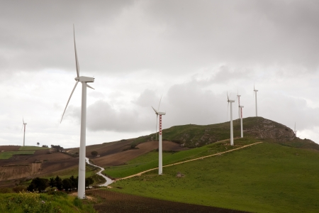airscrew: summer landscape with big wind turbines on green hills, Italy, Sicily Stock Photo