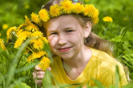 closeup portrait of smiling little girl in dandelion wreath on green grass background photo