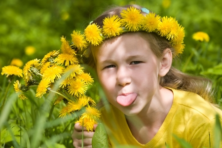 show garden: closeup portrait of little girl in dandelion wreath putting out her tongue Stock Photo