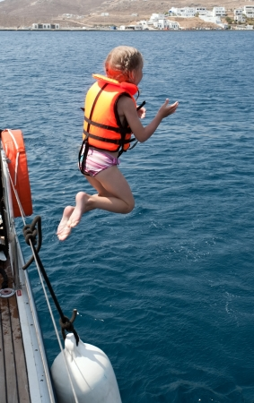 plunge: little girl in life jacket jumping to sea water from yacht deck