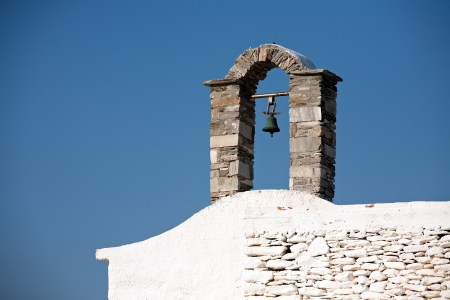 small belfry with one bell of Greek village church on bright blue sky backround
