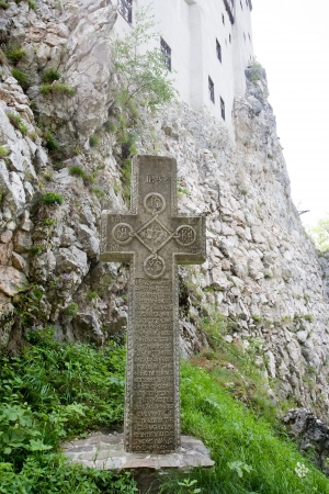 rumania: old stone cross near the wall of Bran medieval castle, Wallachia, Romania