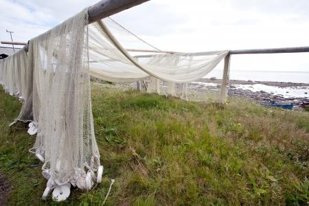 redes de pesca: redes de pesca que cuelgan en la costa del mar para el secado