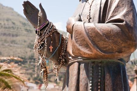castellammare del golfo: beads on a hand of priest statue, Castellammare del Golfo town, Sicily, Italy Stock Photo