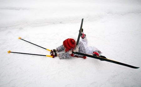 fallen: little girl in skis and ski poles lying on the snow