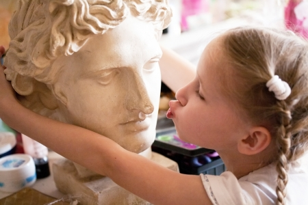 kissing lips: little girl kissing the head of ancient Roman statue