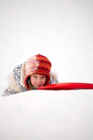 little girl fallen with sled toboggan on snow winter background photo