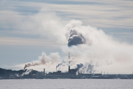 view of big factory with black smoke from its pipe on winter lake coast photo