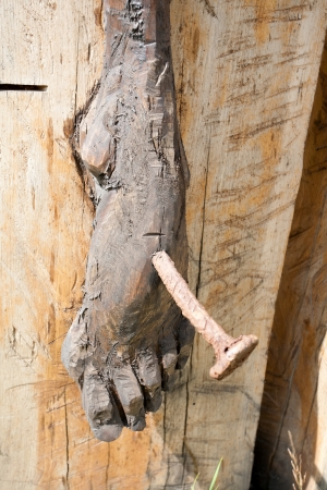 body blood: foot of a wooden Jesus Christ on the cross closeup