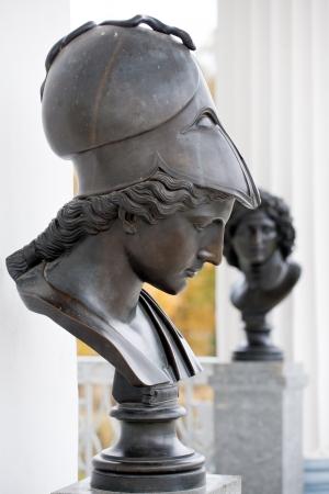 athene: Minerva goddess of war bust black metal statue on white palace walls background