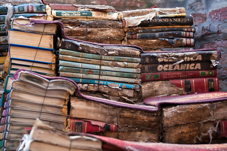 secondhand: piles of many old italian books in second-hand bookseller shop