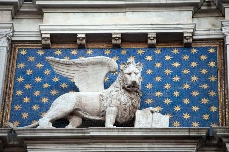 leon con alas: San Marcos león alado con el libro en el reloj de la torre de la fachada, Venecia, Italia Editorial