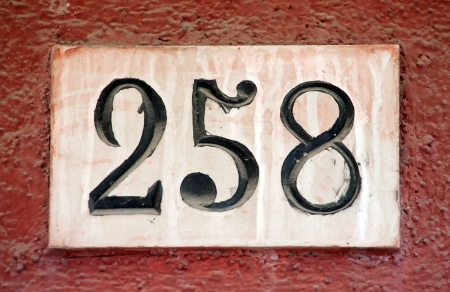 closeup of decorated house number digits sign on the wall photo