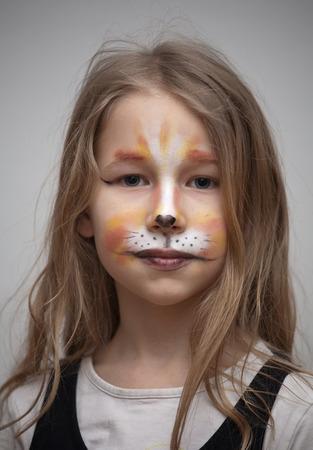 pintura en la cara: closeup retrato de la niña con el gato de la pintura de maquillaje en la cara mirando a la cámara Foto de archivo