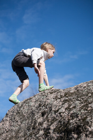 funny little girl climbing the rock on blue sky  photo