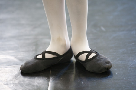 ballet slippers: closeup of child girl feet in ballet slippers on ballroom floor