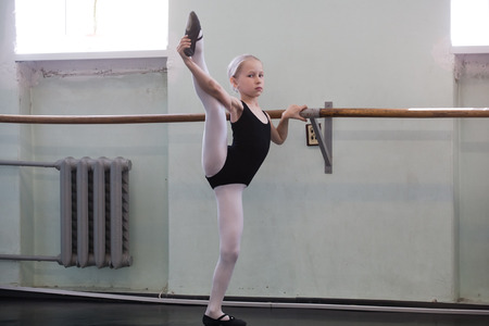 small girl training choreographic exercise standing at ballet barre photo