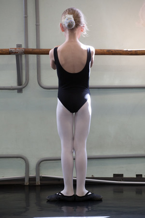 choreography: small girl training choreographic exercise standing at ballet barre, back view