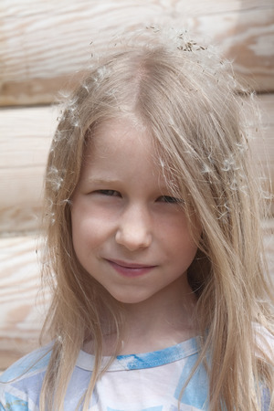 portrait of little caucasian girl on wooden logs wall background photo