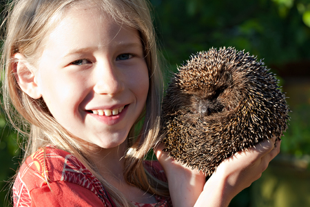 animal in the wild: little smiling girl with cute hedgehog ball in hands Stock Photo