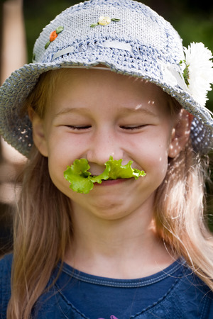funny smiling vegetarian girl with green salad leaf in her mouth photo