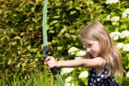 archery: little caucasian girl aiming arrow from big bow closeup on outdoor nature background Stock Photo
