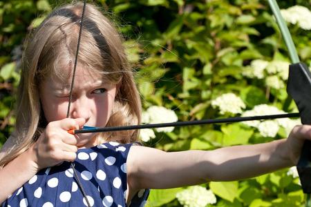 자연, 배경에 큰 활에서 어린 백인 소녀 목표로 화살표