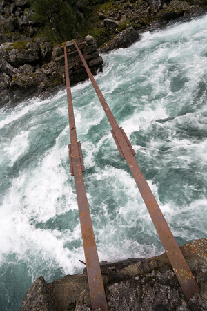 two rusty rails of damaged bridge over mountain tumultuous river Reklamní fotografie