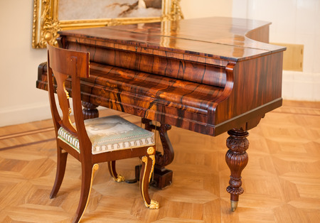 old piano: old big grand piano with chair near it in room interior