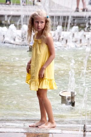 young caucasian girl in yellow summer dress standing before street fountain photo