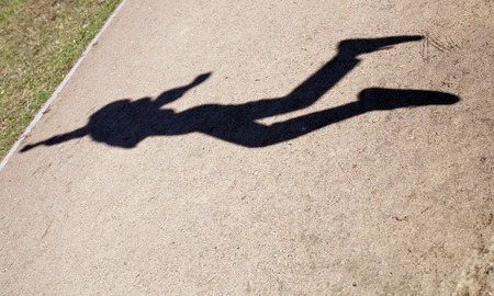 black figure silhouette of human shadow in flying jump photo