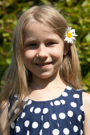 young caucasian girl portrait with camomile flower in the hair photo