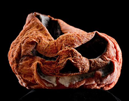 ugly mouth: old and terrible moldy Halloween pumpkin closeup on dark black background Stock Photo