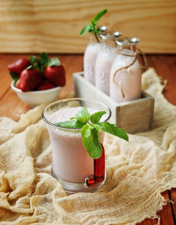 Strawberry milkshake on a rustic wooden table with barry photo