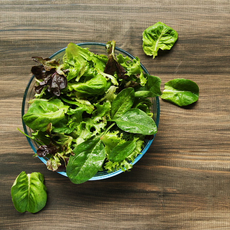 salad in plate: Pan con una ensalada verde sobre tablas de madera, r�stico Foto de archivo