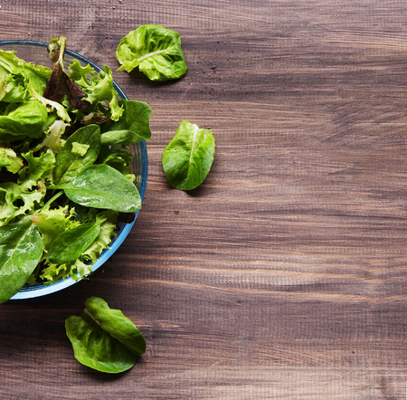 Pan with a green salad on wooden boards,rustic photo
